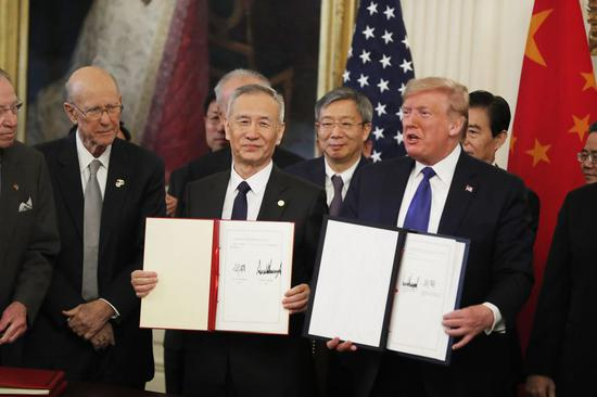 U.S. President Donald Trump and Chinese Vice Premier Liu He, who is also a member of the Political Bureau of the Communist Party of China Central Committee and chief of the Chinese side of the China-U.S. comprehensive economic dialogue, show the signed China-U.S. phase-one economic and trade agreement during a ceremony at the East Room of the White House in Washington D.C., the United States, Jan. 15, 2020. (Xinhua/Li Muzi)
