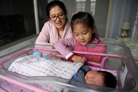 A mother and her daughter watch over the family's newborn baby at an infant healthcare center in Hefei, Anhui province. [Photo/Xinhua]