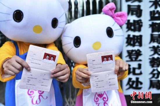 A couple dressing up as cartoon characters shows their marriage certificates. (File photo/China News Service)