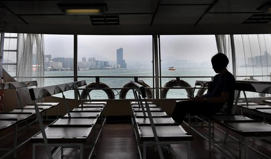 A passenger takes a ferry from Wan Chai ferry pier to Tsim Sha Tsui in Hong Kong in October. Ongoing violence has affected tourism, finance, retail, and other sectors. (Photo/Xinhua)