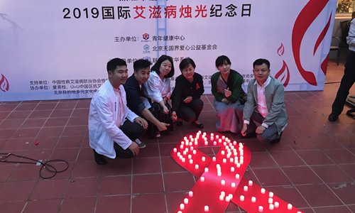Members of the community and volunteers for people living with HIV pose for a group photo at the International AIDS Candlelight Memorial in Beijing on Sunday. (Photo: Dong Feng/GT)