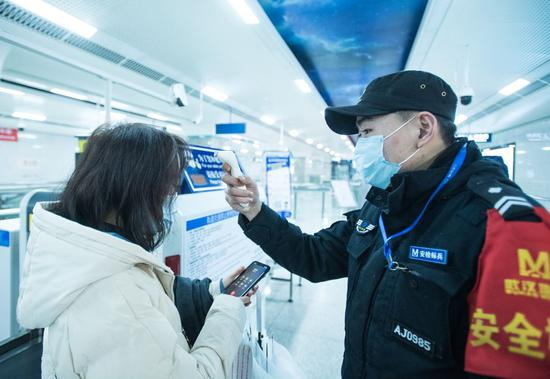 A security staff checks a passenger's body temperature on the subway in Wuhan, central China's Hubei Province, Jan. 23, 2020. (Xinhua/Xiao Yijiu)
