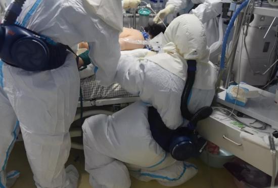 武汉市东湖区人民医院的一名护士跪在地上,为水果机中部湖北省武汉市的病人治病。 /湖北日报