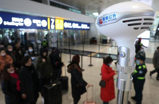 Security staffs check passengers' body temperature at the airport in Wuhan, central China's Hubei Province, Jan. 21, 2020. (Xinhua/Xiao Yijiu)