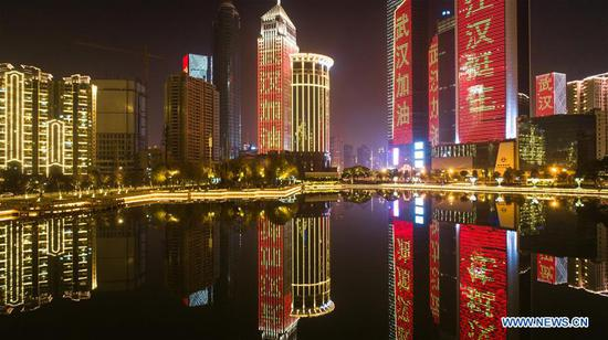 Buildings illuminated with slogans to cheer up Wuhan