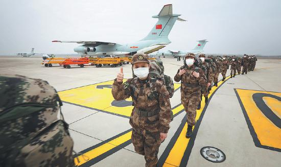 A medical worker in a People's Liberation Army unit gives a thumbs-up upon her arrival at Wuhan Tianhe International Airport in Hubei province on Sunday. Eight PLA aircraft landed with 795 personnel and 58 metric tons of needed supplies. (CHEN XIAODONG / FOR CHINA DAILY)