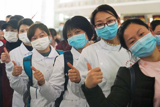 Medical care team members queue to board a plane setting off for central China's Hubei Province, in Nanchang, east China's Jiangxi Province, Feb. 4, 2020. A medical care team comprised of 101 members set off for Hubei from Nanchang to combat the novel coronavirus pneumonia on Tuesday. (Xinhua/Wan Xiang)