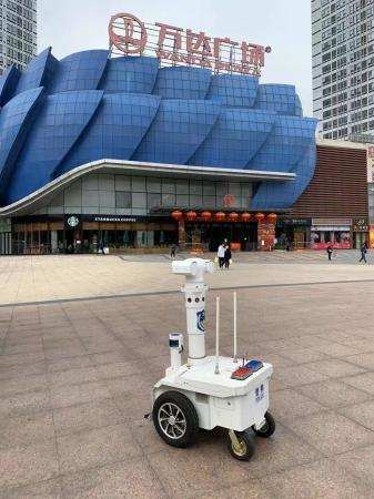 A robot, capable of checking the body temperature of people five meters away, works outside a shopping mall in Guangzhou, Guangdong province to help fight the novel coronavirus. (Photo provided to chinadaily.com.cn)