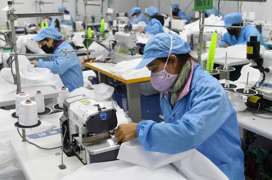 Workers make protective suits at the workshop of a company in Nanning, south China's Guangxi Zhuang Autonomous Region, Feb. 3, 2020. (Xinhua/Lu Boan)