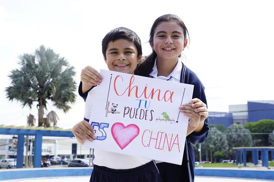 Two children in El Salvador paint to encourage China