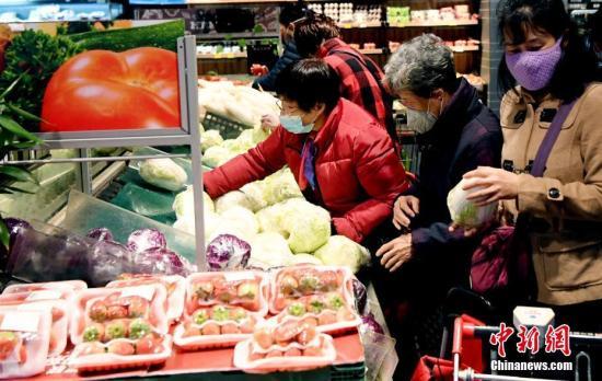 戴着口罩的人在2020年1月27日在中国东南部的福建省福州市的一家超市购买蔬菜。(照片/中国新闻社)