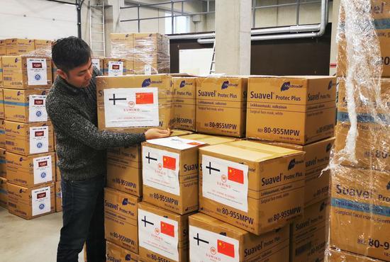 Overseas Chinese checks medical supplies donated to China at a warehouse in Helsinki, Finland, Jan. 31, 2020. (Xinhua/Zhu Haochen)