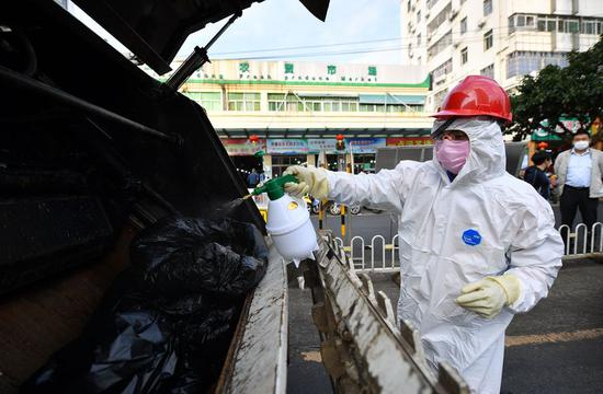 A sanitation worker disinfects bags containing waste facial masks in Haikou, south China's Hainan Province, Feb. 2, 2020. (Xinhua/Guo Cheng)