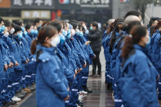 Medical team members from Chongqing are seen on a ceremony before leaving for Xiaogan City of Hubei Province, in southwest China's Chongqing, Feb. 11, 2020. (Photo by Huang Wei/Xinhua)