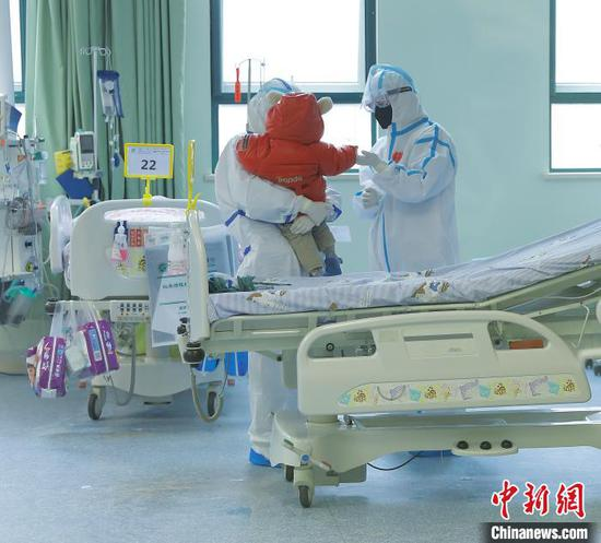 14-month-old says goodbye with doctors after recovery at the Wuhan Children's Hospital, Hubei Province, Feb. 13, 2020. (Photo provided to China News Service)