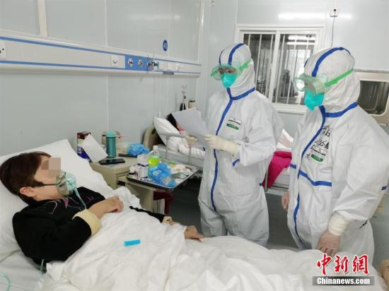 Medical staff visit a patient with confirmed novel coronavirus (COVID-19) infection. (China News Service)