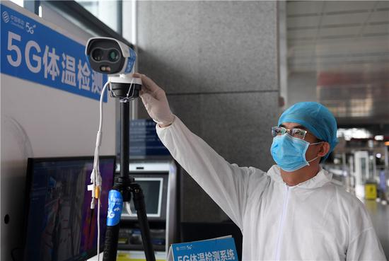 An employee adjusts a 5G-enabled body temperature checking system at the railway station of Nanning, capital of the Guangxi Zhuang autonomous region.[Photo/Xinhua