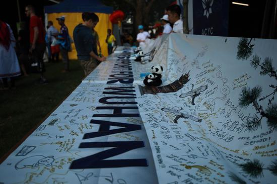 Local people sign their names to express support to China's Wuhan at the 2020 National Multicultural Festival in Canberra, Australia, Feb. 22, 2020. (Photo by Chu Chen/Xinhua)