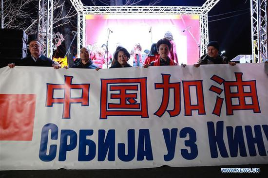 """Serbian Minister of Mining and Energy Aleksandar Antic (1st L), Chinese ambassador to Serbia Chen Bo (C) and Serbian singer Slobodan Trkulja (2nd R) hold a banner written """"Stay Strong China"""" during a concert in support of China in Belgrade, Serbia on Feb. 22, 2020. Hundreds of Serbians and Chinese gathered at a concert at Belgrade Fortress here in the capital on Saturday, offering their solidarity with medical professionals and citizens in Wuhan, the epicenter of the novel coronavirus, and China. (Xinhua/Shi Zhongyu)"""