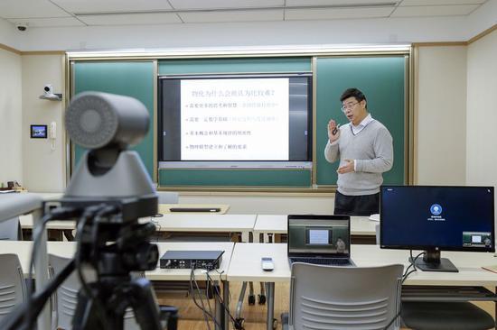 Huang Jianbin, a teacher of Peking University, uses online educational system