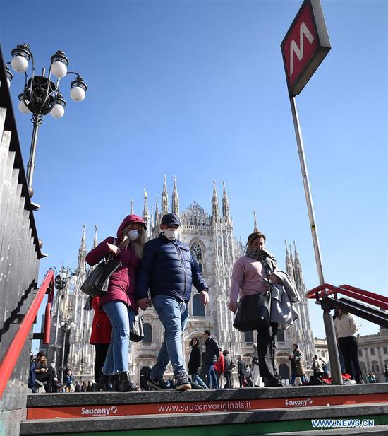 People wearing masks walk into a subway station in Milan, Italy, on Feb. 24, 2020. Six people have died and 222 have tested positive for the novel coronavirus (COVID-19) nationwide in Italy, Angelo Borrelli, chief of Civil Protection Department and Extraordinary Commissioner for the Coronavirus Emergency, told a press conference at 6 p.m. local time on Monday. (Photo by Daniele Mascolo/Xinhua)