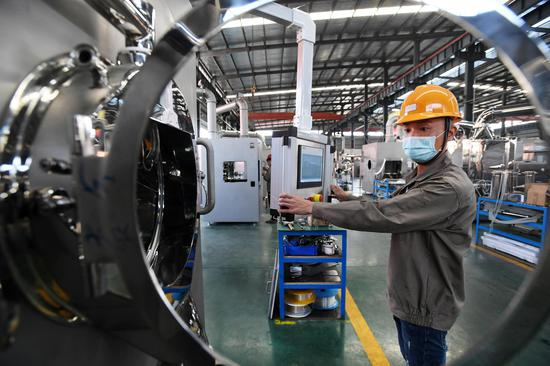 An employee works on a production line to produce dry granulators, which will be supplied to drug manufacturers in Shanghai and other cities to help combat the coronavirus, at Wanshen Pharmaceutical Machinery Co., Ltd. in Yichun, east China's Jiangxi Province, Feb. 24, 2020. (Xinhua/Zhou Mi)