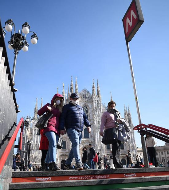 People wearing masks walk into a subway station in Milan, Italy, on Feb. 24, 2020.(Photo by Daniele Mascolo/Xinhua)