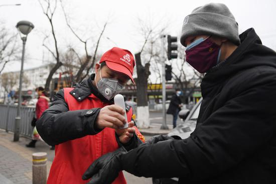 Volunteer Zhang Jianguo (L) takes the temperature of a resident at the entrance of Cheniandian Lane in Beijing, capital of China, Feb. 27, 2020. (Xinhua/Ju Huanzong)