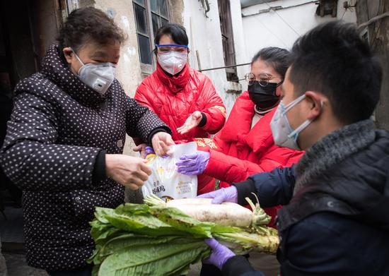 Grid-based community worker Huang Lifang (2nd L) and volunteers Liu Ying (2nd R) and Zhang Qi (1st R) deliver food to a senior citizen living alone in Wuhan, central China's Hubei Province, Feb. 7, 2020. (Xinhua/Xiao Yijiu)