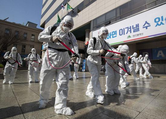 South Korean army soldiers wearing protective suits spray disinfectant in Daegu, South Korea, March 2, 2020.(Photo by Lee Sang-ho/Xinhua)