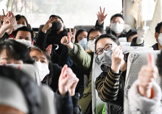 Cured coronavirus patients gesture on the bus home after a 14-day quarantine for medical observation at a rehabilitation center in Wuhan on March 10, 2020. (Xinhua/Cheng Min)