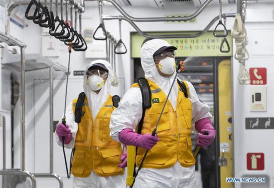 2020年3月11日,工作人员在韩国首尔对地铁列车进行消毒。(摄影:李相浩/新华社)