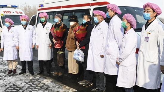 2020年2月11日,三名治愈的COVID-19病人与医护人员在新疆维吾尔自治区乌鲁木齐市新疆维吾尔自治区第六人民医院合影。