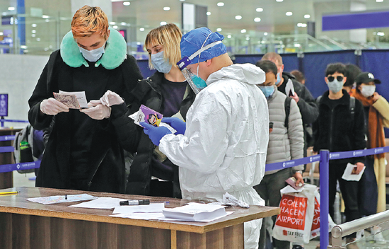 A customs officer checks passengers' health information at Pudong International Airport in Shanghai. (Photo by Yin Liqin/China News Services)