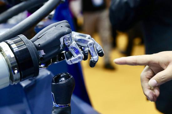 A visitor touches an automated hand at an exhibition during the second CIIE in Shanghai on Nov 6, 2019. [Photo by Zhu Xingxin/chinadaily.com.cn]