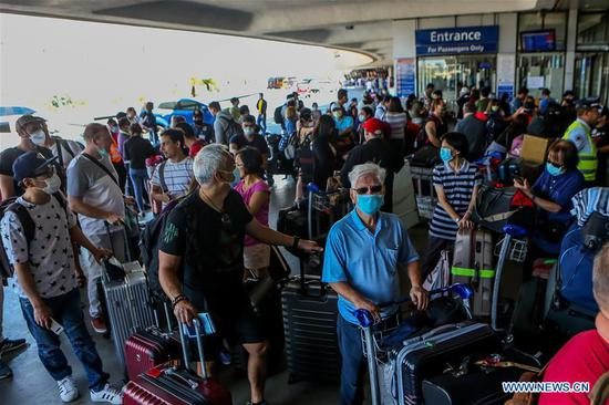 People wearing face masks are seen as they wait for their flight in Ninoy Aquino International Airport (NAIA) in Pasay City, the Philippines on March 19, 2020. COVID-19 cases in the Philippines has risen to 202, the Philippines said on Wednesday. (Xinhua/Rouelle Umali)