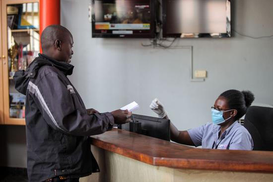 A receptionist wearing a face mask receives a client in Kampala, Uganda, March 18, 2020.(Xinhua/Hajarah Nalwadda)