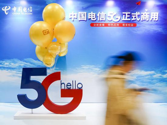 A consumer walks past a poster of commercial 5G applications outside a branch of China Telecom in Beijing, capital of China, Oct. 31, 2019. (Xinhua/Shen Bohan)
