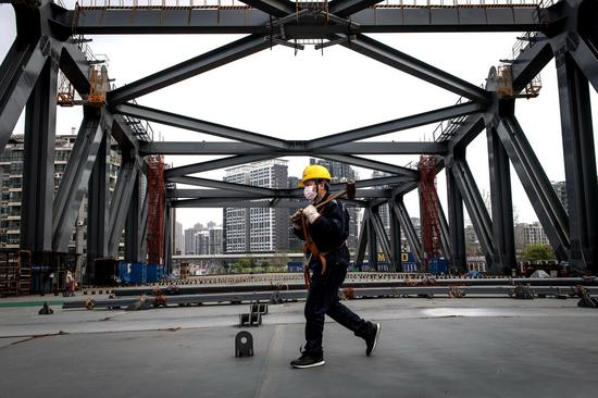 A man works on the No 7 Jianghan Bridge, which resumed construction on March 24 in Wuhan, Hubei province. It will be the seventh bridge crossing the Hanjiang River. (Photo by REN YONG/FOR CHINA DAILY)