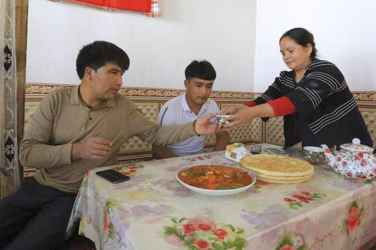 Memettursun Nurdun has dinner with his wife and son at home, March 24, 2020. (Xinhua/Ding Lei)