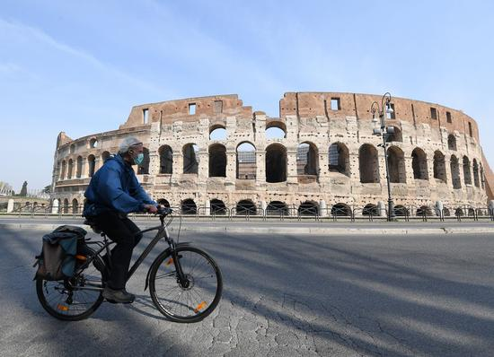 A man wearing a face mask rides a bike in Rome, Italy, March 22, 2020. (Photo by Elisa Lingria/Xinhua)