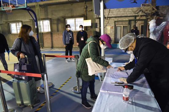 2020年3月25日,一名从湖北归来的妇女(前2楼)在中国首都北京东城区的一个集合点接受了检查。(新华社/陈忠浩)