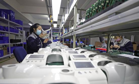 Employees work on the production line of a ventilator manufacturing company in Shenyang, capital of Liaoning province. (Photo/Xinhua)