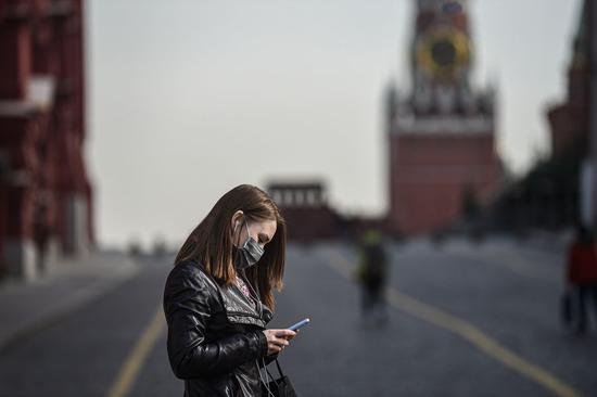 A woman wearing a protective mask looks at her cellphone in Moscow, Russia, on March 27, 2020. (Photo by Evgeny Sinitsyn/Xinhua)