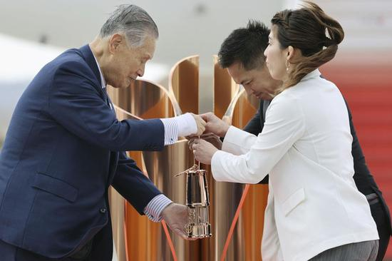 Olympic gold medalists Tadahiro Nomura (C) and Saori Yoshida (R) hand over the flame to President of Tokyo Organizing Committee of the Olympic and Paralympic Games (Tokyo 2020) Yoshiro Mori during the Olympic flame arrival ceremony in Miyagi of Japan, on March 20, 2020. (Kyodo News/Handout via Xinhua)