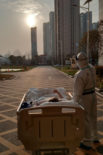 A coronavirus patient and doctor watch sunset outside a hospital in Wuhan, March 5, 2020. (Photo courtesy of Zhongshan Hospital affiliated to Fudan University)
