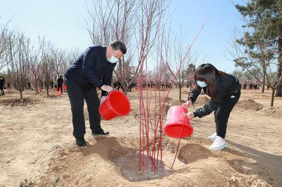 Xi plants trees in Beijing, urging respect for nature