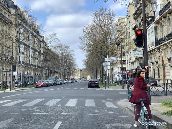 A woman is seen on an empty street in Paris, France, on April 2, 2020.  (Xinhua/Tang Ji)