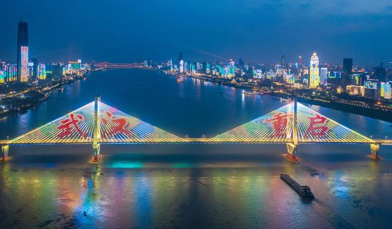 A light show was staged on the No. 2 Wuhan Yangtze River Bridge and along banks of the Yangtze River in Wuhan, April 6, 2020, to celebrate the upcoming lifting of lockdown of the city. (Photo/China News Service)