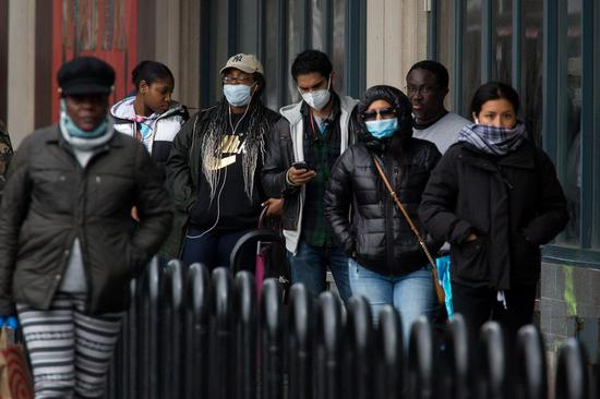 People wearing face masks wait in line outside a grocery store in the Brooklyn borough of New York, the United States, on April 3, 2020. (Photo by Michael Nagle/Xinhua)